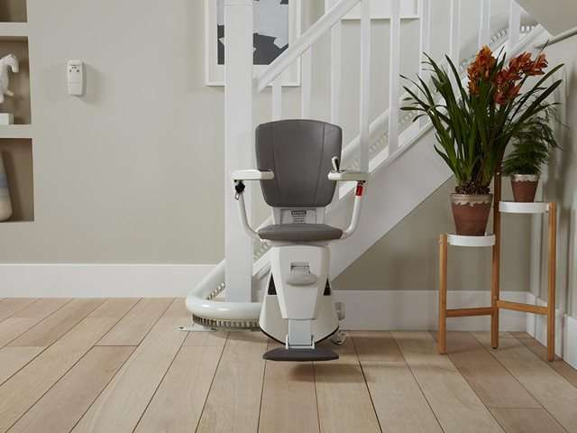 A closer view of a grey coloured upholstery Flow stair lift parked neatly at the bottom of the stairs around a curve to keep the stairs area as clear as possible. The stairlift chair seat, armrests and footrest are all down, so the stairlift is ready for use.