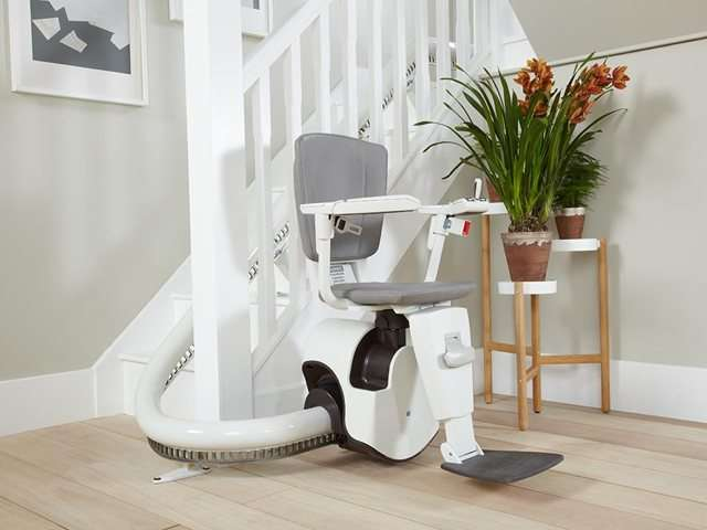 An angle photo of a grey coloured upholstery Flow stair lift parked neatly at the bottom of the stairs around a curve to keep the stairs area as clear as possible. The stairlift chair seat, armrests and footrest are all down, so the stairlift is ready for use as required.