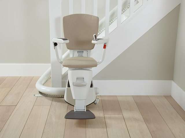 A photo of a beige coloured upholstery Flow stair lift as it is parked at the bottom of the stairs around the curve, to provide free access to the stairs for people who do not need the use of the stairlift. The stair lift chair seat, armrests, and footrest are all in the down position.