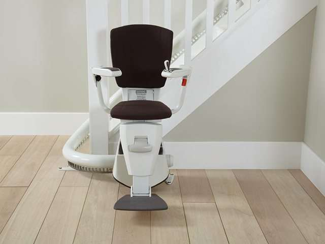 A photo of a dark brown coloured upholstery Flow stair lift as it is parked at the bottom of the stairs around the curve, to provide free access to the stairs for people who do not need the use of the stairlift. The stair lift chair seat, armrests, and footrest are all in the down position.