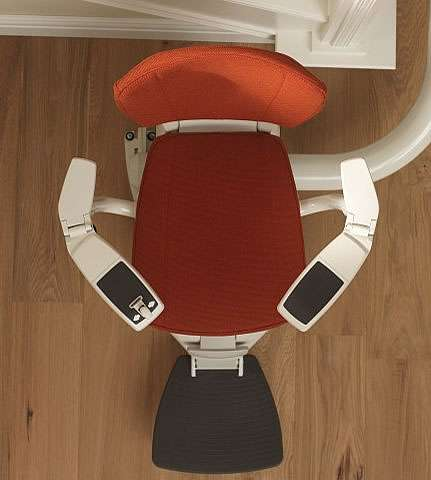 Bird's eye view of red seat of Flow stairlift, with clear view from above of the Flow stair lift seat, back, arm rests and foot rest.