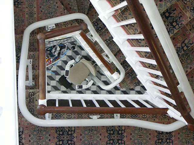 Bird's eye view of curved, angled stairs with multiple bends, showing the path of the stair lift rail, and at the bottom of the stairs, a beige-coloured Flow stairlift chair ready for use.