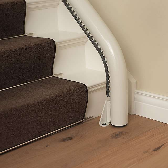 A photo showing how the stair lift rail at the bottom of the stairs curves down and fits neatly to the floor.