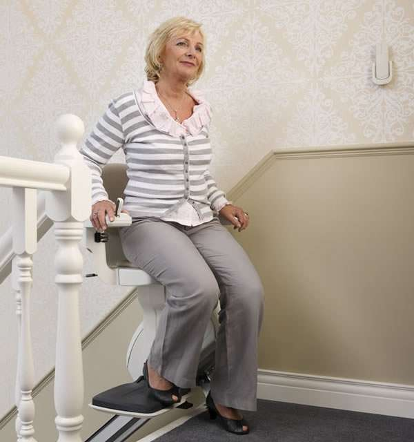 Female user about to get off the cream-coloured Homeglide stair lift after is has arrived at the landing area at the top of straight stairs. User has swiveled the stairlift chair to face inwards to the landing area.