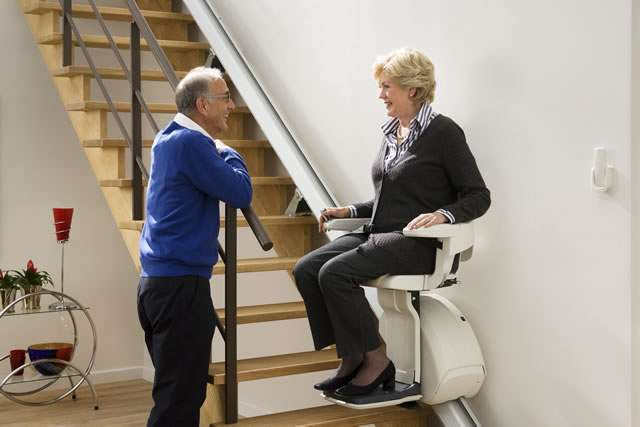 Close-up photo of smiling male and female stair lift users having a conversation. Female user seated on stair lift at the bottom of the stairs looking at standing male user leaning on the bannister.