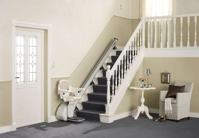 Cream coloured Homeglide stair lift with seat, arm rests and foot rest in down position, parked at the bottom of straight stairs.