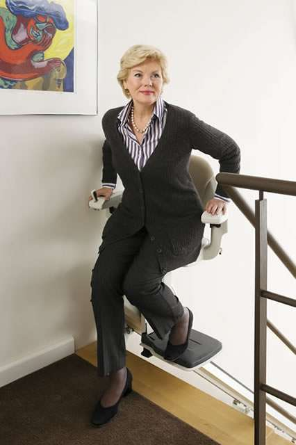 A different angle photo of female stair lift user getting off the stair lifts at the top of the stairs. Stair lift chair facing the landing area.