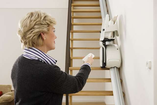 Female user situated at the bottom of the stairs, using the stair lift remote control to send the closed-up stair lift up the stairs, or to bring the closed-up stairlift down the stairs, ready for use.