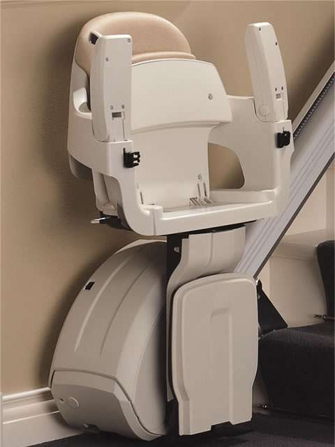 A close-up photo of cream-coloured Homeglide stairlift parked at the bottom of the stairs, with armrest, seat, and footrest all in the up position, providing the maximum space for users who do not require the stairlift to go up and down the straight stairs.