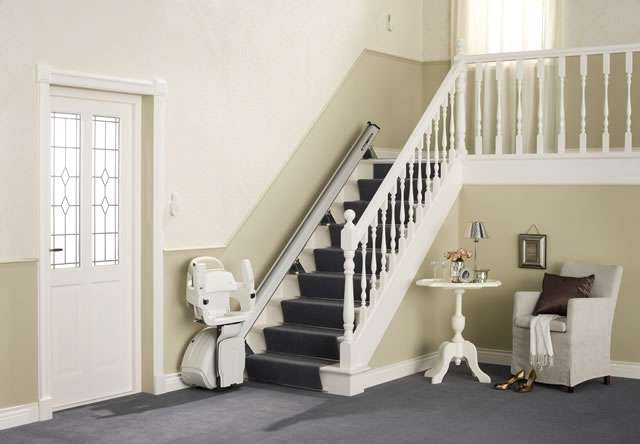 Cream coloured Homeglide stair lift with seat, arm rests and foot rest in up position to allow easy access to the stairs, parked at the bottom of straight stairs.