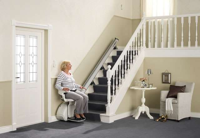 Female user sitting on cream-coloured Homeglide stair lift about to up straight stairs.