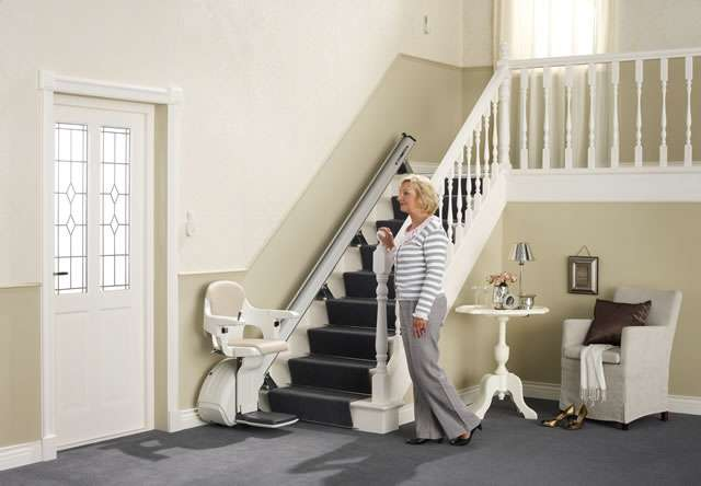 Female user standing near and looking at cream-coloured Homeglide stair lift parked at the bottom of straight stairs. Stairlift seat, armrests and footrest all in the down position, ready for user to sit on the stair lift.