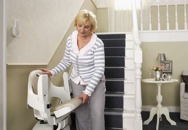 Close-up photo of female user adjusting the seat, arm rests and footrest of cream-coloured Homeglide stair lift parked at the bottom of straight stairs.