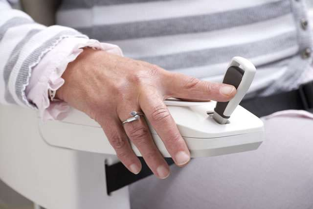 Close-up photo of female user adjusting the armrest joystick control of cream-coloured Homeglide stair lift for straight stairs.