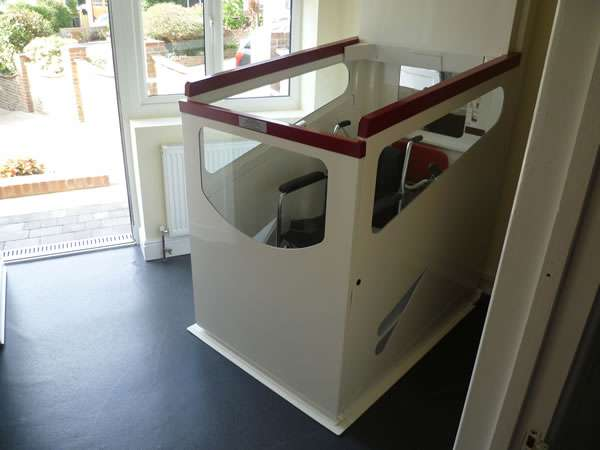 Terry Lifts Harmony through-floor wheelchair lift, with photo taken from an oblique angled view, showing lift at rest on ground floor, with empty wheelchair situated inside