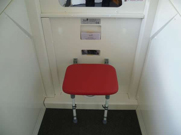 Terry Lifts Harmony through floor wheelchair lift, view from inside the lift cubicle, showing the flip-down seat set to the open position, ready to use