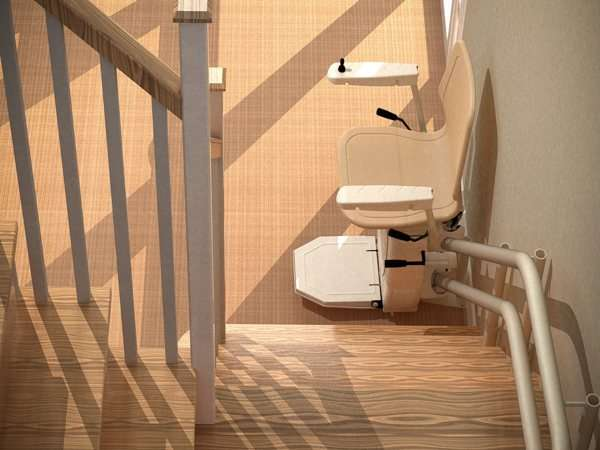 Near vertical bird's eye view, looking down from top of stairs, of beige Dolphin Infinity stairlift parked at the bottom of the stairs, with seat, arm rests and foot rest all in the down position.