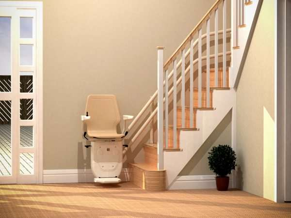 Front view of beige Dolphin Infinity stairlift parked at the bottom of the stairs, with seat, arm rests and foot rest all in the down position.