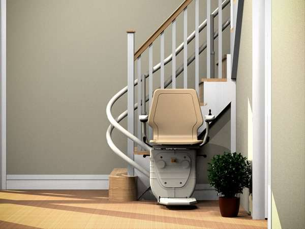 Front view of beige Dolphin Infinity stairlift parked at the bottom of curved stairs, showing that the stairs are not obstructed.