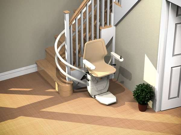 Angled bird's eye view of beige Dolphin Infinity stairlift parked at the bottom of curved stairs, showing that the stairs are not obstructed.