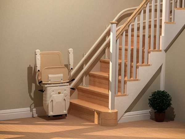 Angled front view of beige Dolphin Infinity stairlift parked at the bottom of straight stairs, with seat, armrests, and footrest in up position, allowing good access to the stairs for people who do not require use of the stair lift.