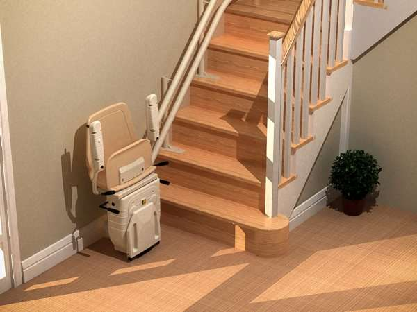 Bird's eye, angled front view of beige Dolphin Infinity stairlift parked at the bottom of straight stairs, with seat, armrests, and footrest in up position, allowing good access to the stairs for people who do not require use of the stair lift.