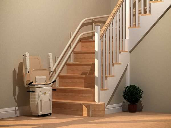 Angled side view of beige Dolphin Infinity stairlift parked at the bottom of straight stairs, with seat, arm rests, and foot rest in up position, allowing good access to the stairs for people who do not require use of the stair lift.