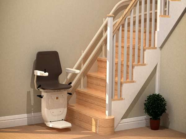 Angled view of brown Dolphin Infinity stair lift, parked at the bottom of stairs, with seat, arm rests and footrest in the down position.