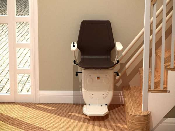 Further back front view of brown Dolphin Infinity stair lift, parked at the bottom of stairs, with seat, arm rests and footrest in the down position.