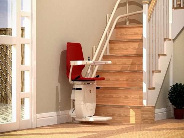 Side view of red Dolphin Infinity stair lift parked at bottom of stairs with seat, arm rests and foot rest in the down position.