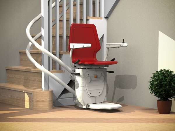 Red Dolphin Infinity stair lift parked at bottom of curved stairs with seat, arm rests and foot rest in the down position, showing how the stair lift is parked around the curve, providing easy access to the stairs for people who do not need the stairlift.