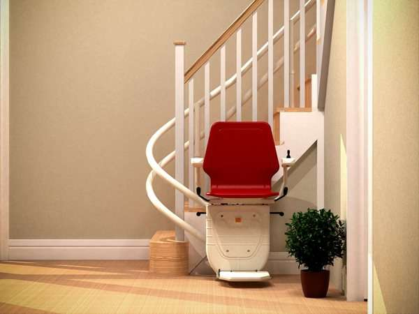 Close up front view of red Dolphin Infinity stair lift parked at bottom of curved stairs with seat, arm rests and foot rest in the down position, showing how the stair lift is parked around the curve, providing easy access to the stairs for people who do not need the stairlift.