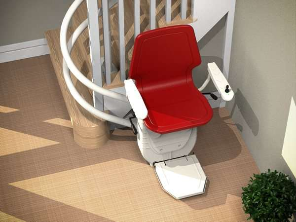 Bird's eye angled view of red Dolphin Infinity stair lift parked at bottom of curved stairs with seat, arm rests and foot rest in the down position, showing how the stair lift is parked around the curve, providing easy access to the stairs for people who do not need the stairlift.