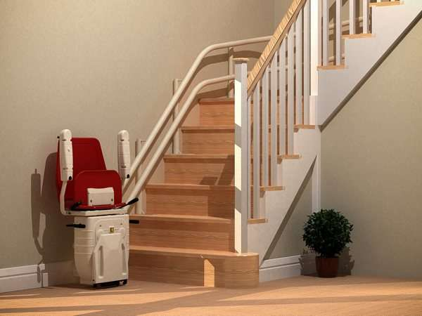 Bird's eye angle further back view of red Dolphin Infinity stair lift parked at bottom of stairs with seat, arm rests and foot rest in up position.