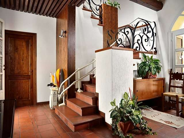 Platinum Curve curved stairlift, parked at bottom of stairs with arm rests, seat, and footrest in up position.