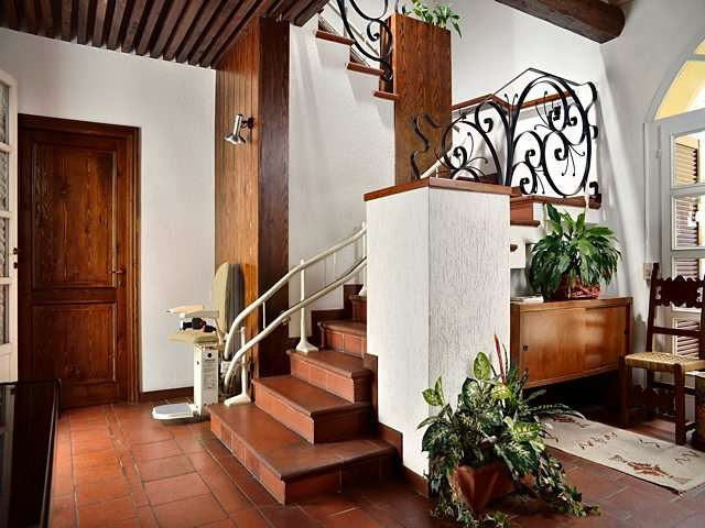 Platinum Curve curved stairlift, parked at bottom of stairs with arm rests, seat, and footrest in down position.