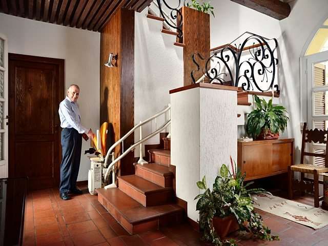Male user lowering the seat, armrests and footrest of Platinum Curve curved stairlift, parked at bottom of stairs.