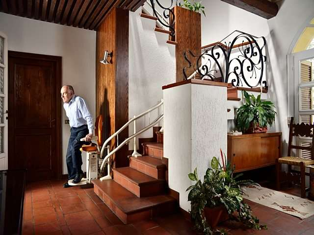 Male user about to sit on Platinum Curve curved stairlift chair, parked at bottom of stairs.