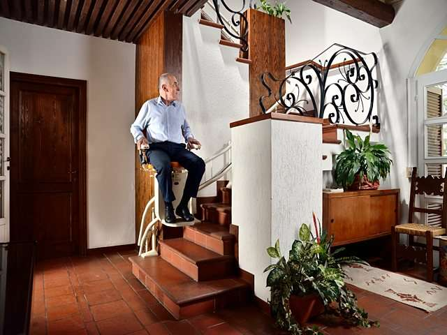 Male user sat on Platinum Curve curved stairlift chair as it goes up the stairs.