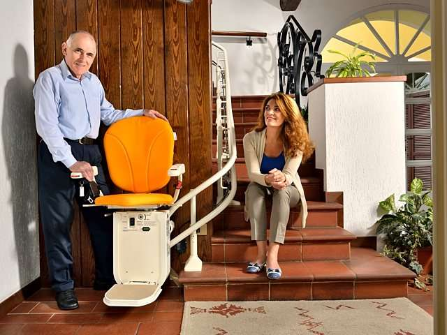 Male user facing the camera stands next to Platinum Curve curved stairlift at the bottom of the stairs. Female user sitting in the space on the stairs next to the stairlift chair.