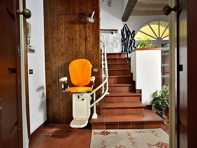 Platinum Curve curved stairlift chair at the bottom of the stairs facing the camera.