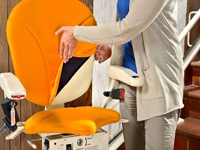 Female user pulls back the orange coloured upholstery cover of the Platinum Curve seat back to show how easily the covers can be removed and laundered.