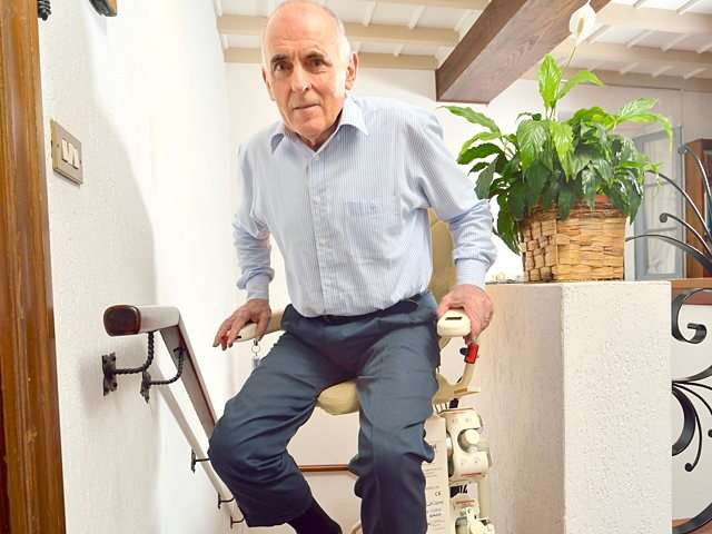 The male user preparing to get off the chair of the Platinum Curve stair lift as it has arrived on the landing at the top of the stairs.
