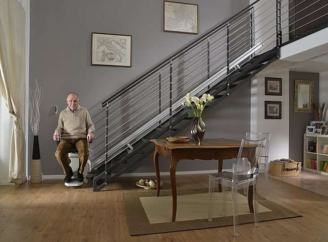 User standing next to Platinum Horizon stair lift parked at bottom of stairs.