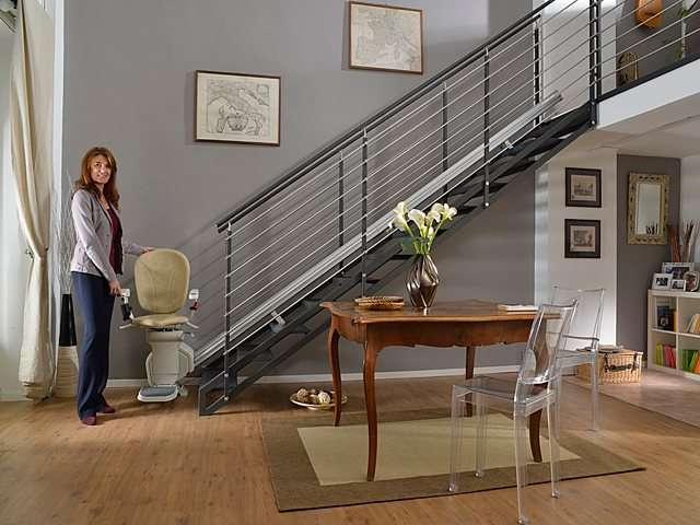 Female user standing next light coloured upholstery Platinum stair lift parked at bottom of stairs.