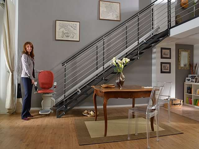 Female user standing next red coloured upholstery Platinum stair lift parked at bottom of stairs.