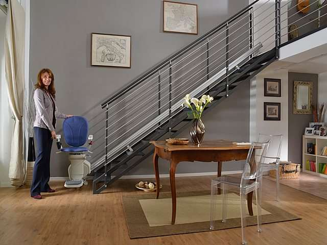 Female user standing next blue coloured upholstery Platinum stair lift parked at bottom of stairs.
