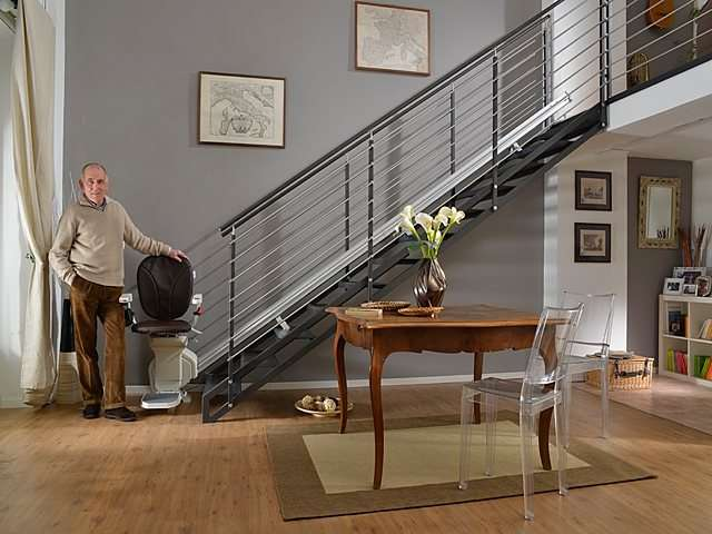 Male user standing next brown coloured upholstery Platinum stair lift parked at bottom of stairs.
