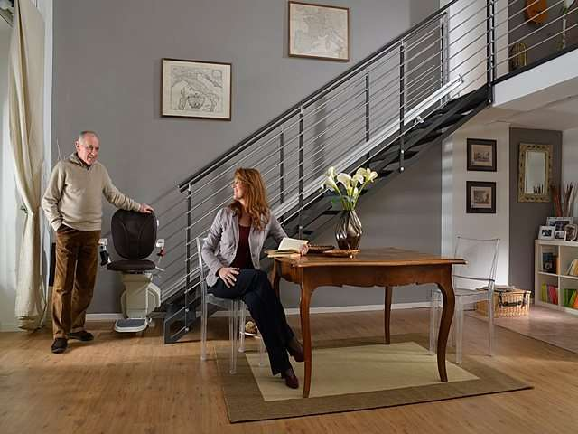 Male user standing next brown coloured upholstery Platinum stair lift parked at bottom of stairs talking with female user seated at table nearby.