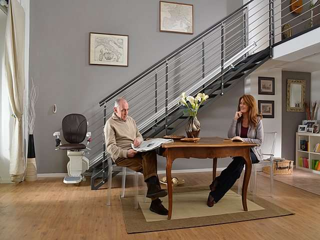 Male and female users seated at table next to brown coloured Platinum Horizon stair lift parked at bottom of stairs.